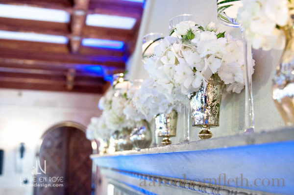 la-vie-en-rose-wedding-white-arrangement-blue-up-lighting-hydrangea-fireplace-mantle-floating-candle-mercury-vase-reception-powel-crosley-estate-sarasota-florida