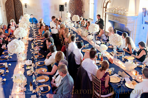 la-vie-en-rose-wedding-white-tall-arrangement-feasting-table-blue-up-lighting-gold-chiavari-chairs-reception-powel-crosley-estate-sarasota-florida