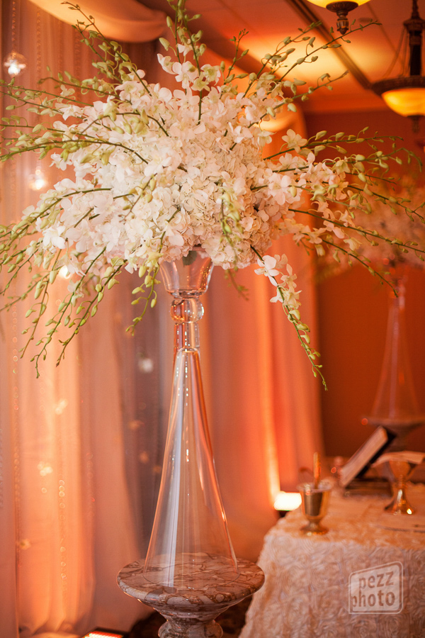 la-vie-en-rose-wedding-arrangement-orchids-hanging-lights-glow-drapery-clear-vase-the-tampa-club