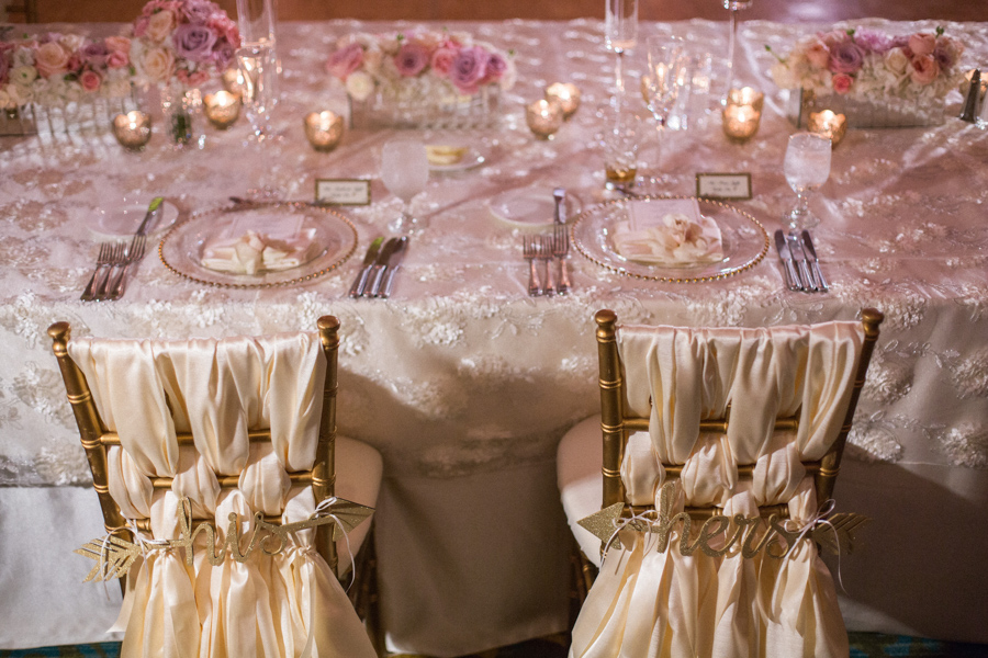 la-vie-en-rose-tampa-bay-saint-petersburg-wedding-hotel-reception-church-ceremony-candles-decor-floral-arrangements-table-specialty-linens-dupioni-flower-overlay-bride-and-groom-chair-decor-chair-ties-braided-his-and-hers-mirrored-vase-glass-centerpieces-tall-low-crystal-candelabra-wedding-party-roses-hydrangeas-spray-roses-peonies-garden-rose-pink-tones-blush-eucalyptus-gold-chiavari-chairs-gold-beaded-chargers-ivory-napkins-romantic-elegant-the-vinoy