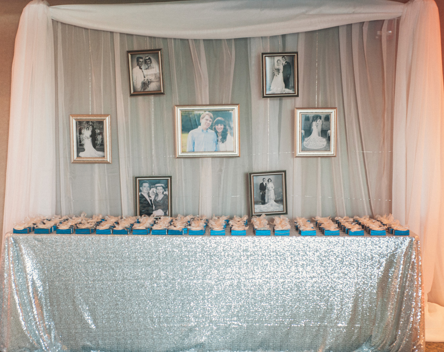 la-vie-en-rose-tampa-bay-Clearwater-wedding-reception-party-favors-william-dean-chocolates-blue-box-white-ribbon-bow-silver-sequin-overlay-linen-white-drapery-sheer-picture-frames-memories-memoir-bride-and-groom-romantic-elegant-Ruth-Eckerd-Hall