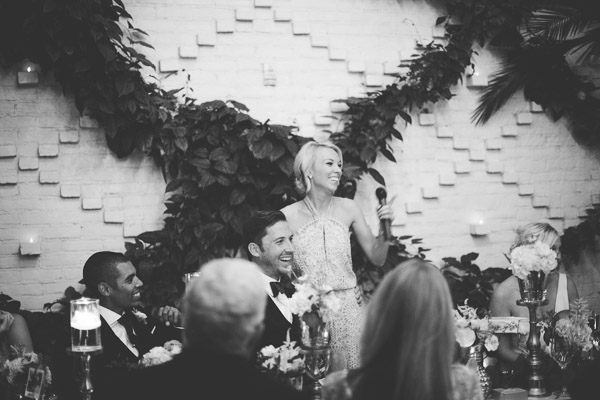 la-vie-en-rose-tampa-bay-Florida-wedding-bride-groom-speech-reception-backdrop-flowers-garland-greenery-candles-floral-arrangements-white-blooms-trendy-fashion-blush-ivory-elegant-The-Oxford-Exchange